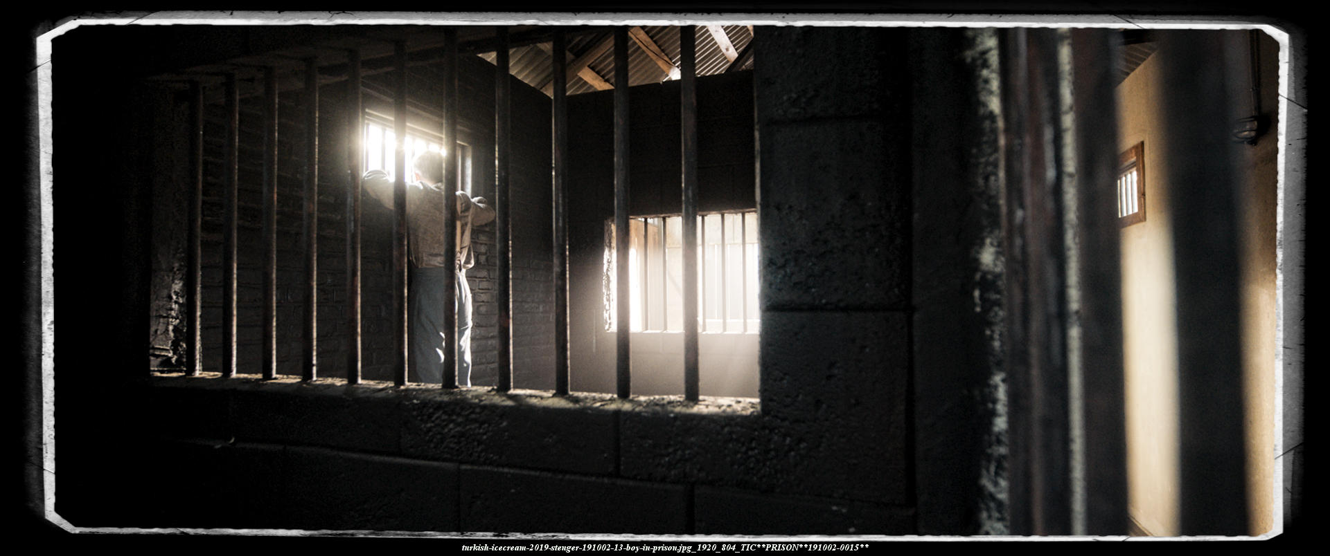 turkish-ICECREA;-James Farley looking out of his prison cell through bars-wide shot
